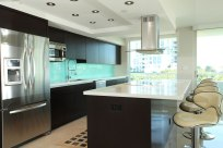 Modern kitchen in dark finish with white bench tops
